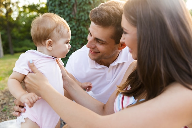 Família jovem e alegre com uma menina passando um tempo juntos