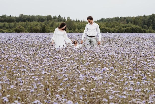Família jovem e bonita com um menino descansando em um campo de flores