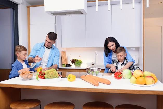 Família jovem e elegante com dois filhos preparando um café da manhã vegetariano saudável com legumes frescos na cozinha