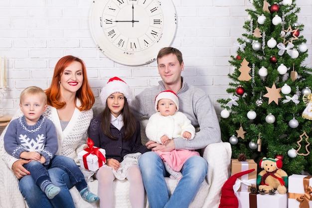 Família jovem e feliz com caixas de presente na frente da árvore de natal