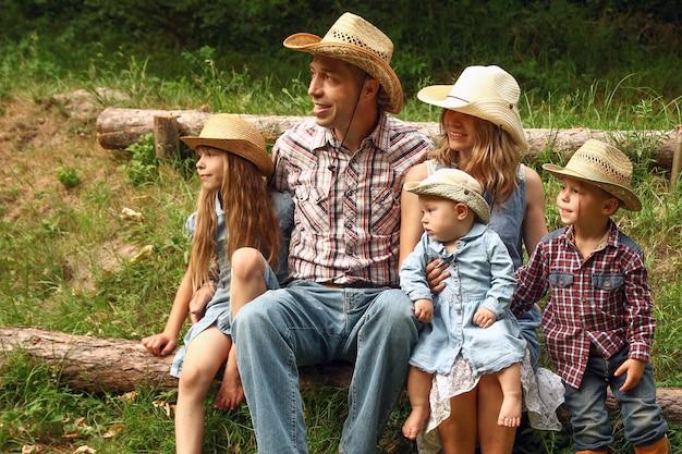 Família jovem e feliz com crianças cowboys