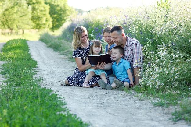 Família jovem e feliz com crianças lendo a bíblia