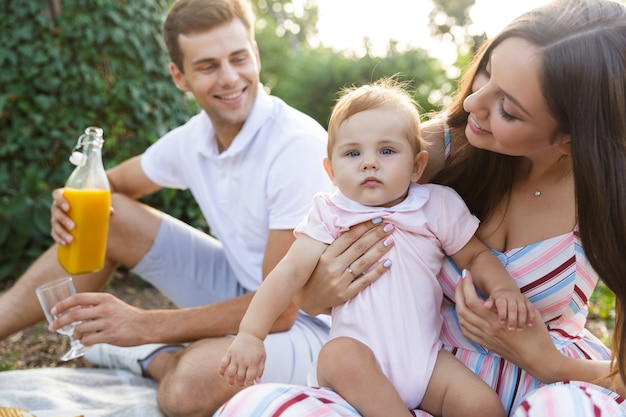 Família jovem e feliz com uma menina passando um tempo juntos
