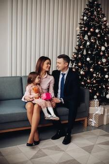 Família jovem e feliz comemora ano novo juntos perto da árvore de natal