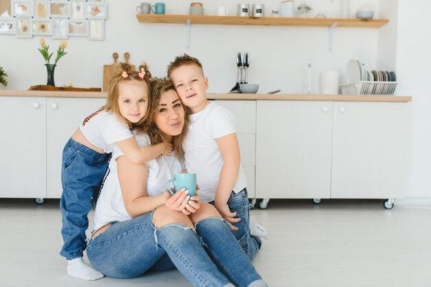 Família jovem e feliz, mãe com filhos pequenos sentada no chão da cozinha