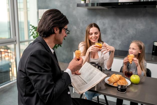 Família jovem e feliz tomando café da manhã em casa