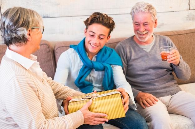 Família jovem e idosa alegre dando um presente no natal