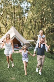 Família jovem em boho casual wear, pai, mãe e duas filhas de mãos dadas e correndo
