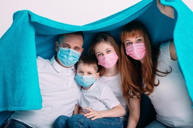 Família jovem em máscaras médicas durante a quarentena em casa.