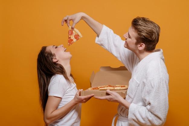Família jovem em roupas para casa em quarentena com pepperoni de pizza italiana, alimenta um ao outro, boas relações familiares, conceito de família engraçado