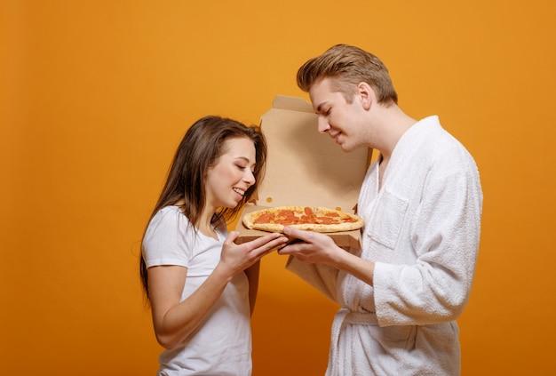 Família jovem em roupas para casa em quarentena com pizza italiana pepperoni boas relações familiares