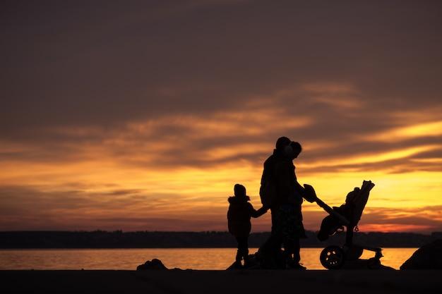Família jovem em silhueta contra um pôr do sol do oceano