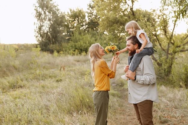 Família jovem em um passeio na natureza é feliz