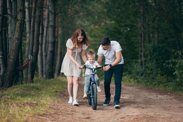 Família jovem em um piquenique na floresta, marido, esposa e filho pequeno, ensina o filho a andar de bicicleta