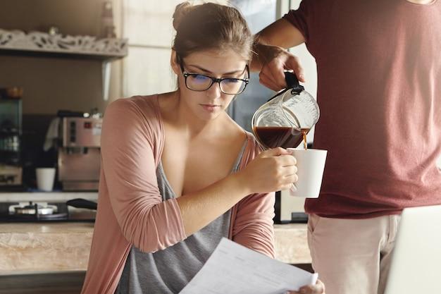 Família jovem enfrentando problemas de dívida. mulher atraente usando óculos lendo jornal do banco com expressão séria e frustrada