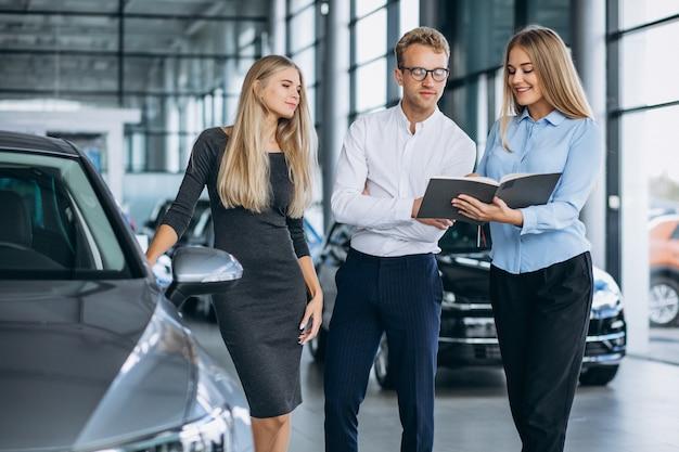Família jovem, escolhendo um carro em uma sala de exposições