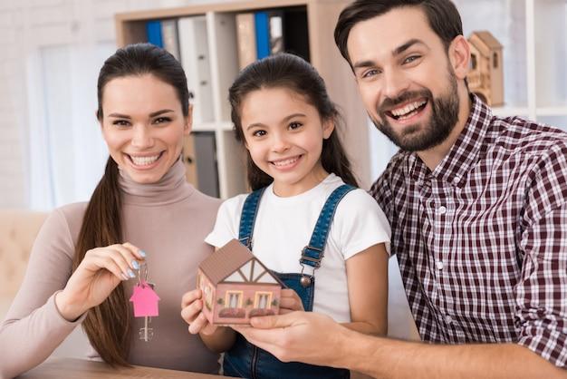 Família jovem está feliz em comprar casa nova