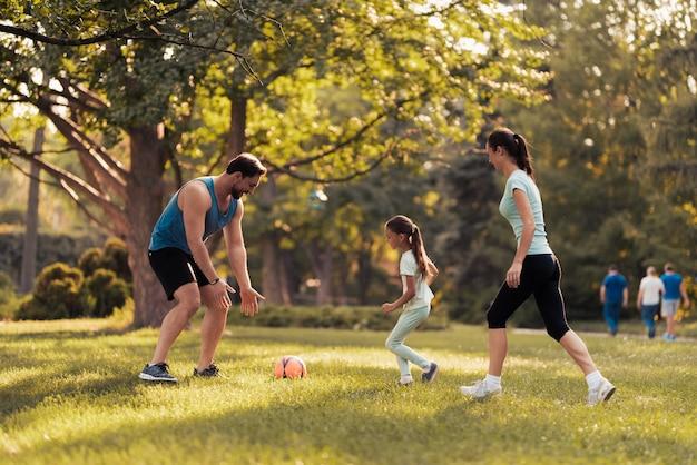 Família jovem está jogando futebol com bola de futebol vermelha.