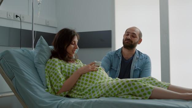 Família jovem falando sobre parto em enfermaria de hospital