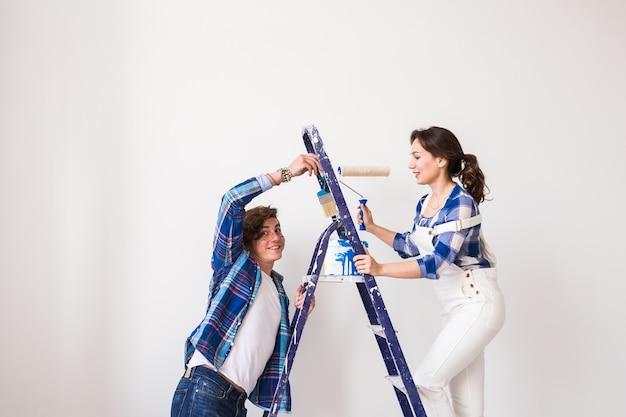 Família jovem fazendo reparos, pintando paredes juntos e rindo.