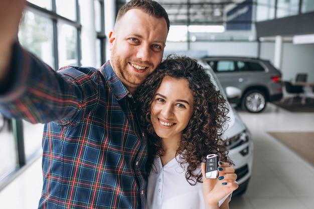 Família jovem fazendo selfie em um show room de carro