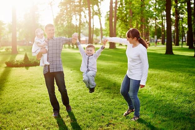 Família jovem feliz caminha no parque de verão
