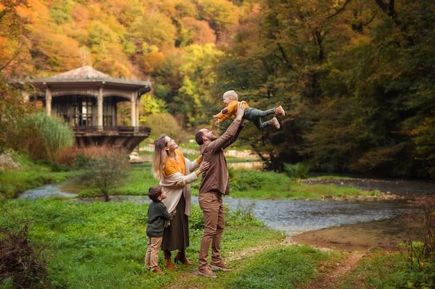 Família jovem feliz com dois filhos em uma caminhada no outono na floresta junto ao rio.