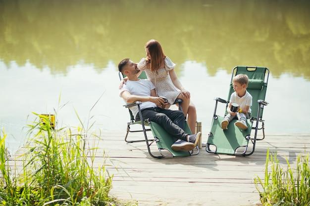 Família jovem feliz com filhos da criança, descansando sentados em cadeiras de acampamento dobráveis sobre o lago em um píer de madeira ao ar livre. passar o tempo de lazer juntos no pontão do acampamento com as crianças na natureza. floresta de férias