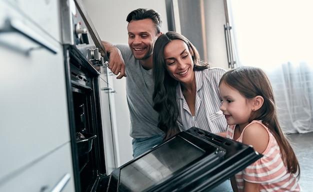 Família jovem feliz com sua filha pequena é espiar no forno enquanto cozinha bolos na cozinha.