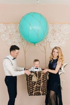 Família jovem feliz comemora o primeiro aniversário da criança. o bebê tem 1 ano de idade. o conceito de uma festa infantil com balões