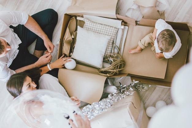 Família jovem feliz comemora o primeiro ano do bebê e desembalar presentes em casa no interior luminoso, vista de cima