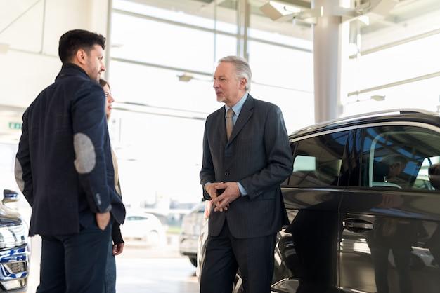 Família jovem feliz conversando com o vendedor e escolhendo seu novo carro em um showroom