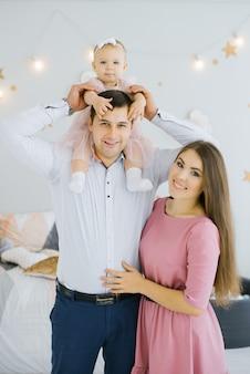 Família jovem feliz e alegre com uma filha pequena, que se senta nos ombros de seu pai. pais felizes e infância