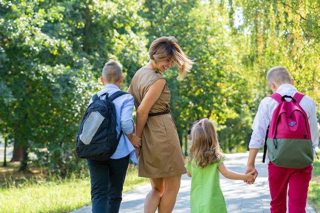 Família jovem feliz, mãe com três filhos, passear no parque. conceito de estilo de vida saudável