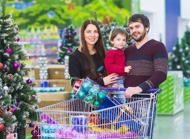 Família jovem feliz no supermercado escolhe presentes para o ano novo.