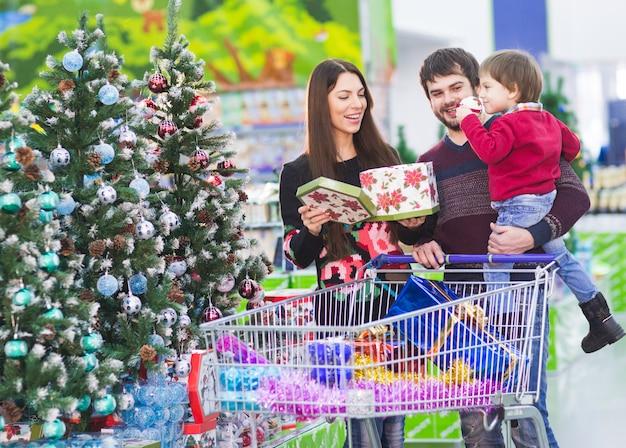 Família jovem feliz no supermercado escolhe presentes para o natal
