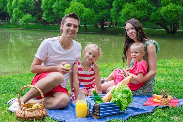 Família jovem feliz piqueniques ao ar livre perto do lago