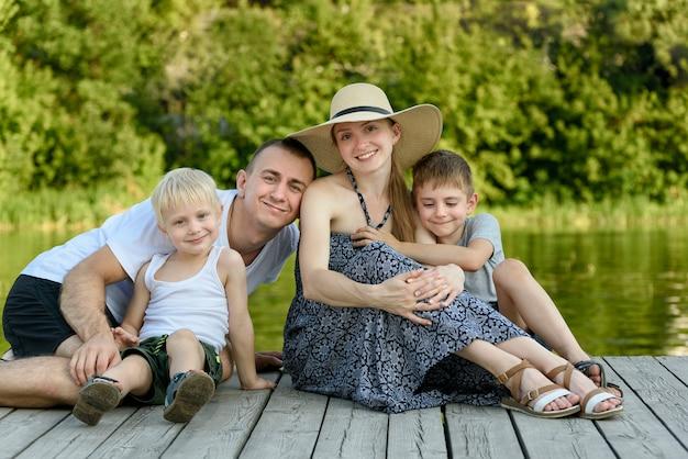 Família jovem feliz, sentado no cais do rio