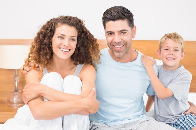Família jovem feliz sorrindo para a câmera na cama