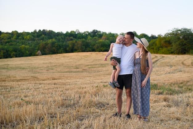 Família jovem feliz. um pai com um filho pequeno nos braços e uma mãe grávida.