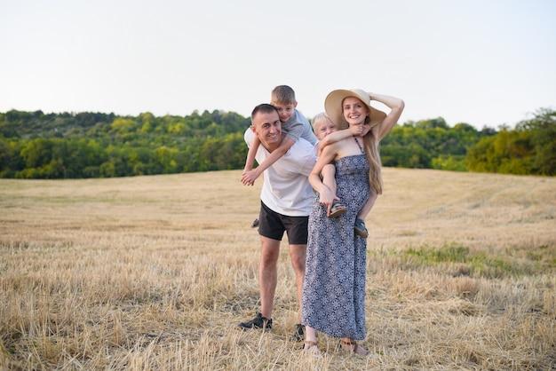 Família jovem feliz. um pai, uma mãe grávida e dois filhos pequenos nas costas. campo de trigo chanfrado. hora do sol