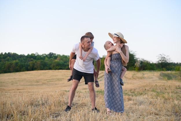 Família jovem feliz. um pai, uma mãe grávida e dois filhos pequenos nas costas. campo de trigo chanfrado