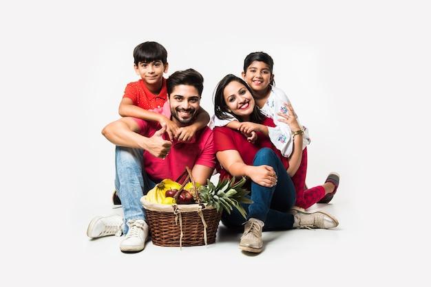 Família jovem indiana de quatro pessoas que vai para o piquenique - sentado sobre um fundo branco com cesta de frutas, tapete, futebol e bebidas. foco seletivo