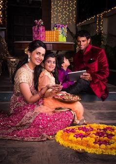 Família jovem indiana fazendo flores rangoli ou organizando diyas para a noite do festival de diwali na varanda com presentes e bokeh ao fundo