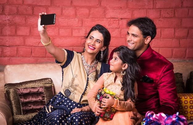 Família jovem indiana tirando selfie ou auto-fotografia em casa com caixas de presente na noite do festival de diwali.