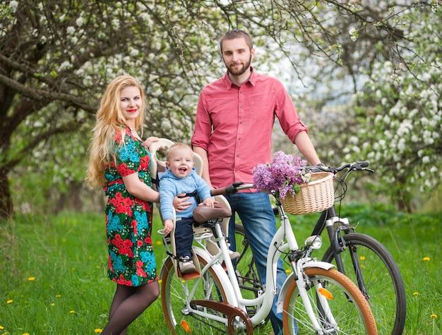 Família jovem, ligado, um, bicycles, em, a, primavera, jardim