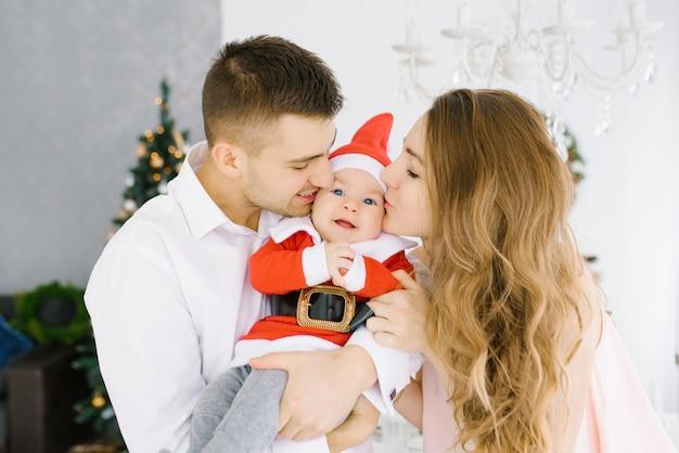 Família jovem: mamãe e papai beijam as bochechas do filho de seu filho