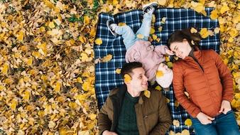 Família jovem, mentindo, ligado, foliage outono, parque