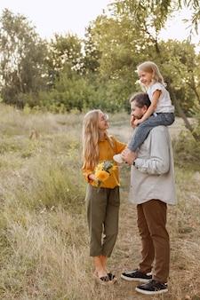 Família jovem na natureza em uma caminhada três são felizes