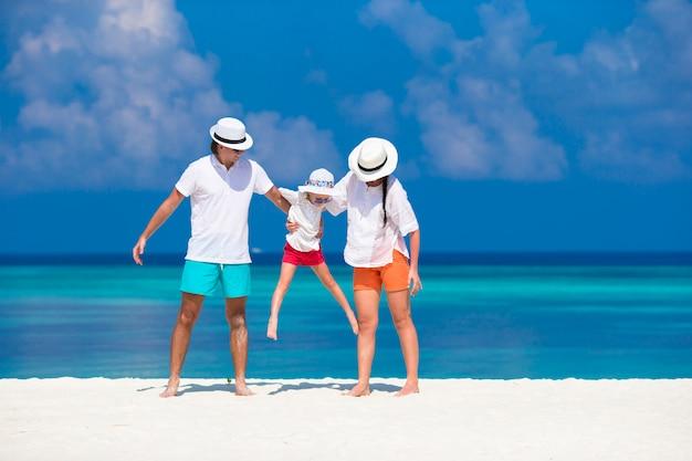Família jovem na praia branca durante as férias de verão